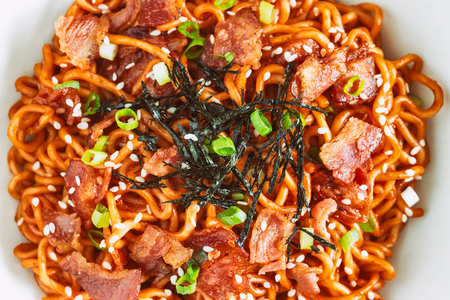 Close up Korean hot and spicy instant noodle in black and white bowl topped with bacon, sesame, seaweed and chopped scallion served with kimchi on wood table. Homemade delicious asian food concept.
