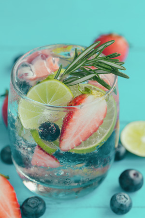 Infused water made from blueberry strawberry and lemon in sparkling mineral water look so freshness and healthy.Mixed fruit mojito on blue wood table with copy space. Summer refreshing drink concept.