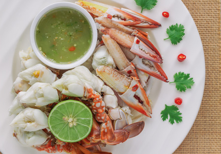 Steamed crab meat prepared for ready to eat with Thai style spicy dipping sauce on white plate in top view flat lay with copy space for background or wallpaper. Delicious homemade seafood concept. Stock Photo