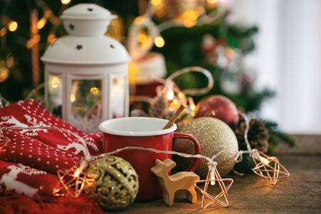Christmas decoration with red cup of chocolate, red scarf, white lantern, star blinker, balls and bauble reindeer on wood table with copy space. Bokeh Christmas tree wallpaper for xmas celebration.