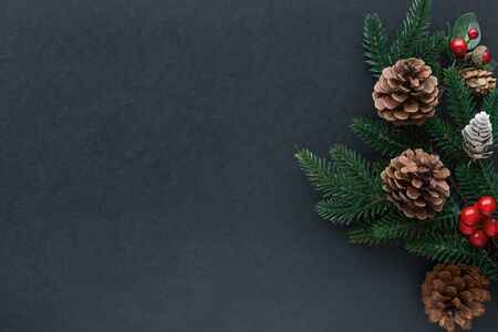 Isolated black granite table decorate with pine leaves, pine cones and holly balls in Christmas theme concept. Luxury vintage background in top view flat lay with copy space for Christmas wallpaper.