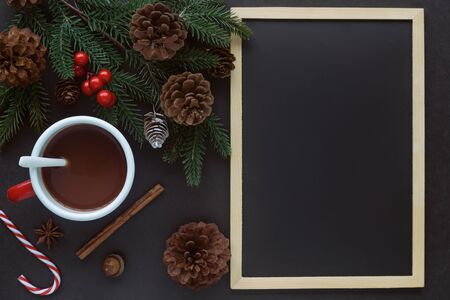 Black granite table decorate with blackboard or chalkboard, pine leaf and cones and cup of chocolate in Christmas concept. Background in top view flat lay with copy space for Christmas wallpaper.