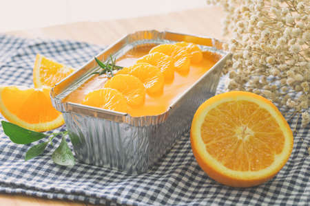 Fresh baked sweet and delicious mandarin orange sponge cake decoration with orange jelly sauce and orange pulp in aluminum foil loaf put on wood table in side view. Homemade bakery concept for cafe. 版權商用圖片