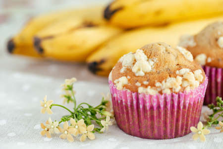 Piece of banana crumble and sesame cupcake or muffin in mini pink cup on table with copy space. Banana cupcake topping with crumbles so sweet and tasty. Homemade bakery with simply delicious concept.