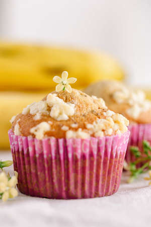 Piece of banana crumble and sesame cupcake or muffin in mini pink cup on table in vertical. Banana cupcakes topping with crumbles so sweet and tasty. Homemade bakery with simply delicious concept.