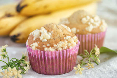 Piece of banana crumble and sesame cupcake or muffin in mini pink cup on table in close up view. Banana cupcake topping with crumbles so sweet and tasty. Homemade bakery with simply delicious concept.