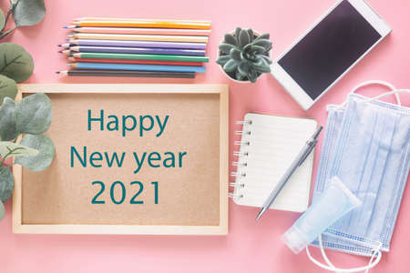 Happy New Year 2021 on wooden letter board with stationery, smartphone, mask and hand sanitizer on pastel pink background in top view flat lay. Concept to present new normal behavior in new year.