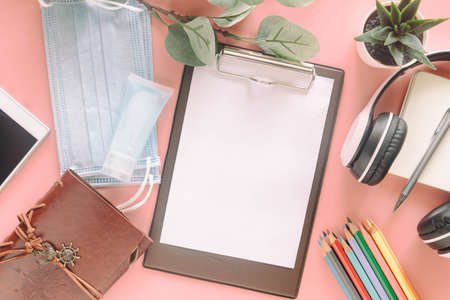 Blank white paper on clipboard with stationery, mask and hand sanitizer on pastel pink background. Concept to present new normal lifestyle activities past covid-19 pandemic.