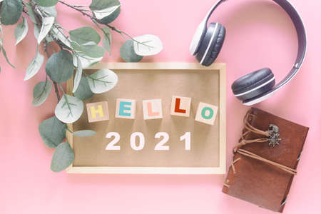 Wooden blocks on letter board in words Hello 2021 on pastel pink background with travel note and headphone in top view flat lay. New year season greetings and travel concept. 版權商用圖片