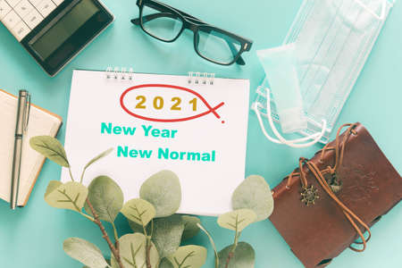 White note with word 2121 New Year New Normal with stationary, medical masks and hand sanitizer on pastel blue background to present new normal lifestyle post covid-19 pandemic. Health concept.