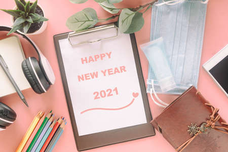 Word Happy New Year 2021 on clipboard with stationery, mask and hand sanitizer on pastel pink background. Concept to present new normal lifestyle activities past covid-19 pandemic.