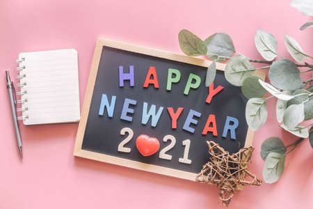 Wooden colorful alphabet on wood letter board in words Happy New Year 2021 on pastel pink background with stationery, leaf, star and red heart in top view flat lay. New year season greetings concept.