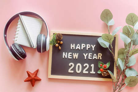 Wooden alphabet on wood letter board in words Happy New Year 2021 on pastel pink background with stationery, leaf, red star and headphone in top view flat lay. New year season greetings concept. 版權商用圖片
