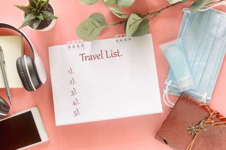 White note with word Travel List with stationary, smartphone, headphone, medical masks and hand sanitizer on pastel pink background. Concept to present travel list in new normal post covid-19 pandemic