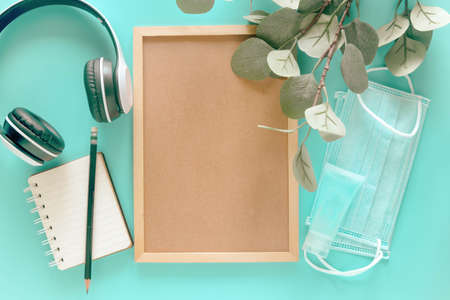 Blank wooden letter board with stationery supplies, medical masks and hand sanitizer on pastel blue background to present new normal behavior or lifestyle post covid-19 pandemic. Health concept.