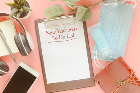 Word New Year 2021 To Do List on clipboard with stationery, mask and hand sanitizer on pastel pink background. Concept to present to do list in new year 2021, new normal post covid-19 pandemic. 版權商用圖片
