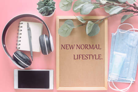 New Normal Lifestyle on wooden letter board with stationery, smartphone, mask and hand sanitizer on pastel pink background in top view flat lay. Concept to present new normal lifestyle in new year.
