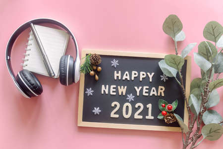 Wooden alphabet on wood letter board in words Happy New Year 2021 on pastel pink background with stationery, leaf, snowflake and headphone in top view flat lay. New year season greetings concept.