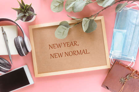 New Year New Normal on wooden letter board with stationery, smartphone, mask and hand sanitizer on pastel pink background in top view flat lay. Concept to present new normal lifestyle in new year.