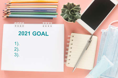 White note with word 2121 GOAL with stationary, smartphone, medical masks and hand sanitizer on pastel pink background to present goal list in year 2021. New year and new normal concept.
