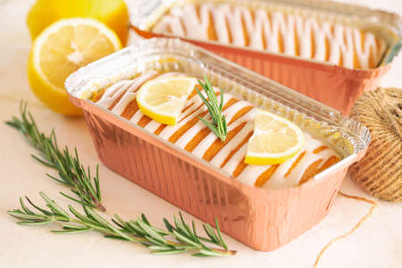 Lemon butter cake or pound cake top with lemon icing glaze decorated with lemon sliced and rosemary leaves in aluminum foil loaf on table. Delicious taste with sweet and sour. Homemade bakery concept.