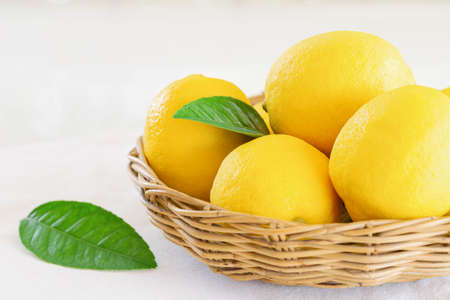Group of whole organic lemon in wood basket on white background. Fresh lemon have high vitamin C and delicious sour taste for lemonade or cooking. Citrus or citron fruit concept.