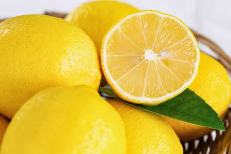 Close up group of whole and cut organic lemon in wood basket on white background. Fresh lemon have high vitamin C and delicious sour taste for lemonade or cooking. Citrus or citron fruit concept. 版權商用圖片
