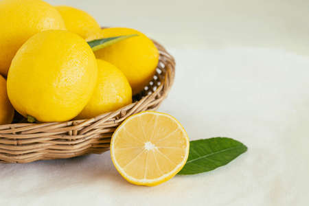 Group of whole and cut organic lemon in wood basket on white background. Fresh lemon have high vitamin C and delicious sour taste for lemonade or cooking. Citrus or citron fruit concept. 版權商用圖片