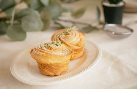 Homemade fresh baked cruffin sprinkle with icing or powdered sugar decorate with thyme leaf on white plate. Cruffin is a mixed of flaky layer croissant and muffin in muffin shape. Modern trend bakery. 版權商用圖片