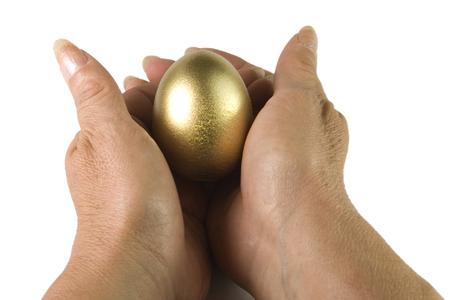 makelaardij: handen een goud en glans ei nesten Stockfoto
