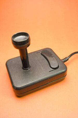 orenge: black video joystick from 80s on orenge background Stock Photo