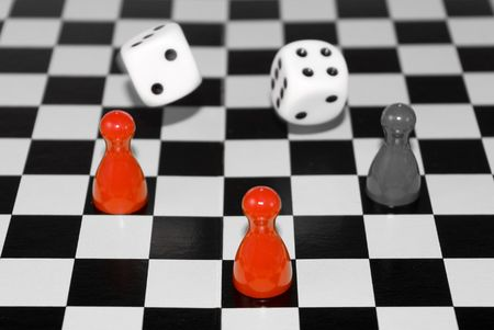 colorized: red colorized dices on a chess board Stock Photo
