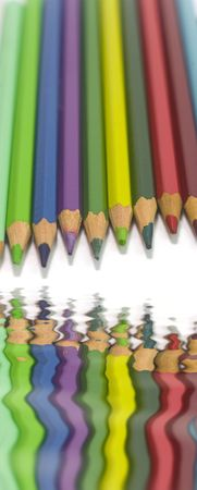 colorful pencils on white background with water reflect