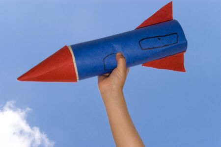 Hand of kid holding a hand made rocket photo