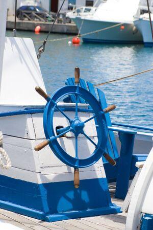 rope bridge: old blue sailer and wheel on caribbean sea