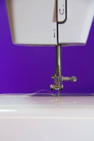 white sewing machine in purple background photo