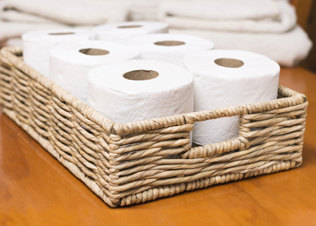 Toilet paper rolls on wicker basket Foto de archivo