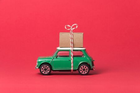 Green travel car side on red, with gift box on top