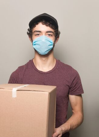 Delivery young men with box  wearing a face mask vertical  写真素材