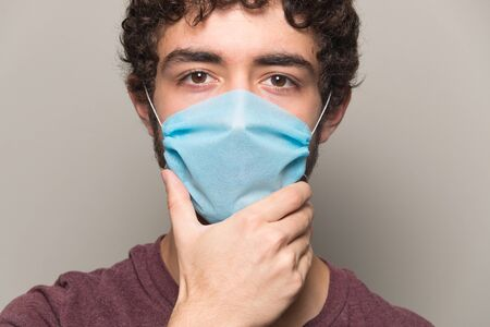 Boy wearinf and hold face mask with hand Stockfoto