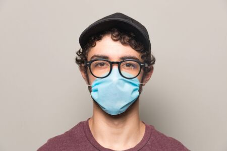 Young person wearing a face mask hat and glasses