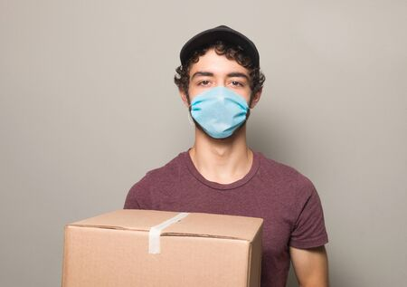 delivery boy wearing face mask with card box, vertical shot