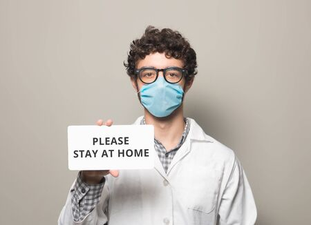 Doctor with face mask holding a sign with text please say at home 写真素材