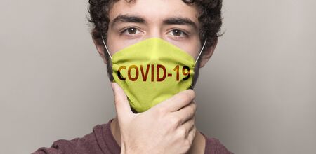 Men face mask hand with text Covid-19 写真素材