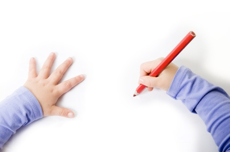 Little girl hands drawing with a red pencil in a white background