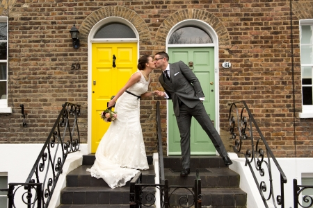 Happy couple kissing on their wedding day in front of their dream home in London photo