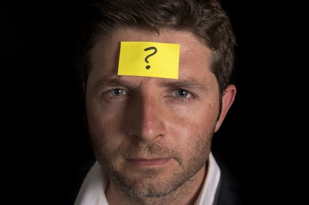 Business man with a yellow posit note on his face with a question mark written on it  photo