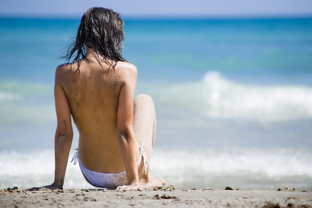 topless brunette: Topless Woman sitting with her back facing the camera, in the sand wearing a white bikini with the sea in the back ground