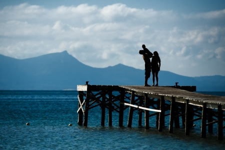 Silhouette of a family at the sea in a summer day. The father is holding his son in his arms photo