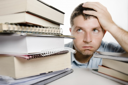 Young Man Overwhelmed and frustrated among a pile of books and notebooks on the desk